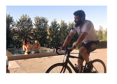 Dan Blizerian training on his bike by the pool with babes